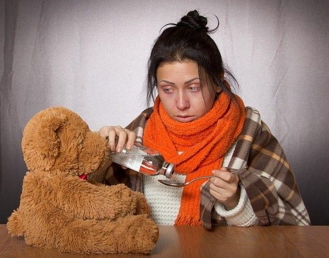 Erkältete Frau mit roten Augen, Schal, Hustensaft und tröstendem Teddybär