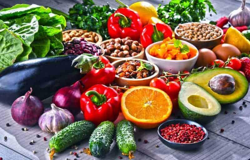 Gesunde, natürliche und bunte Ernährung mit Obst, Gemüse und Nüssen auf Holztisch gegen Entzündungen im Körper