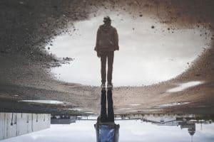 Person mit hängenden Schultern gespiegelt in großer Pfütze