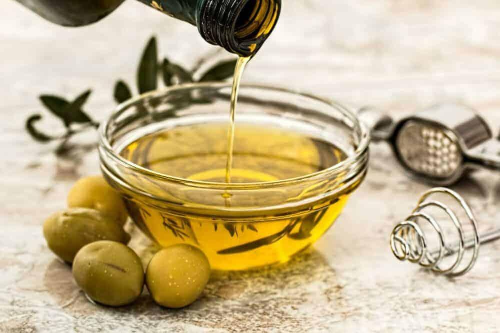 Oliven und Olivenöl in Glasschale auf weißem Hintergrund