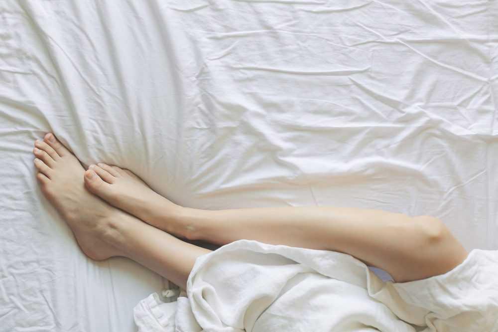 Beine, die unter einer Bettdecke hervorschauen