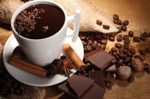 Weiße Porzellantasse mit heißem Kakao, Zimtstangen, Nelken und Schokolade auf braunem Holztisch