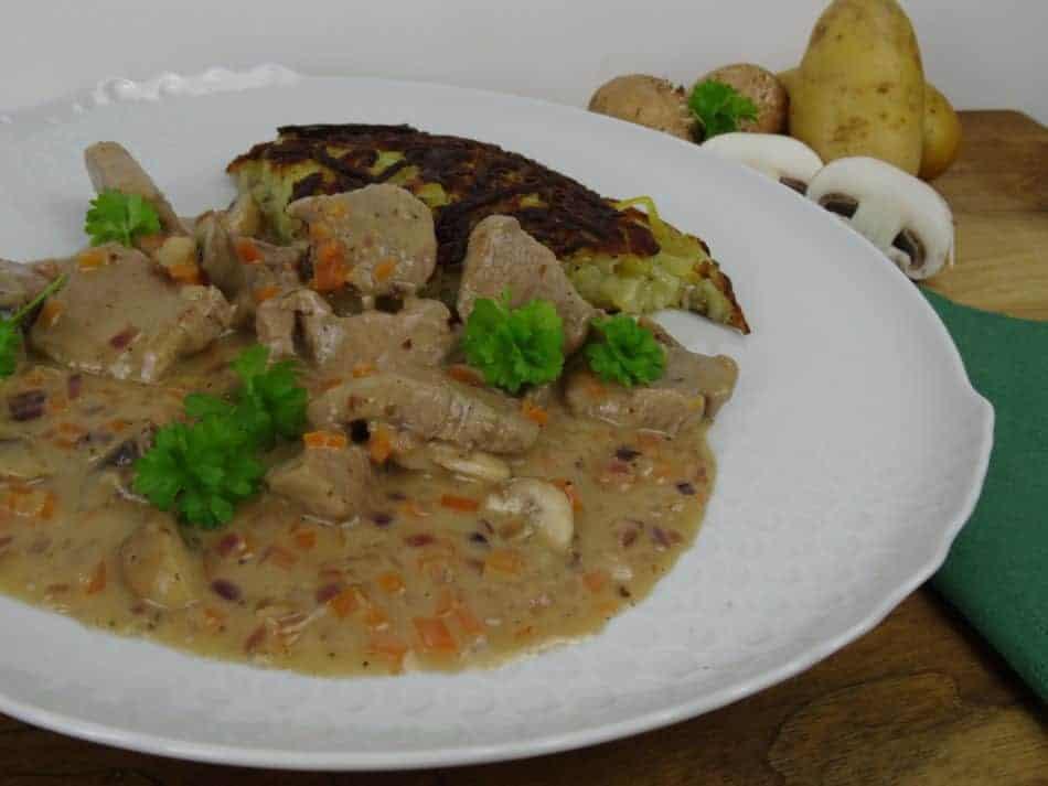 Weisser Teller mit Sauce und Roesti im Hintergrund Kartoffeln und Pilze, alles auf Holz