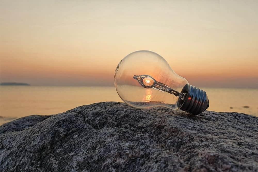 Glühbirne fängt letzte Sonnenstrahlen auf Stein am Strand ein