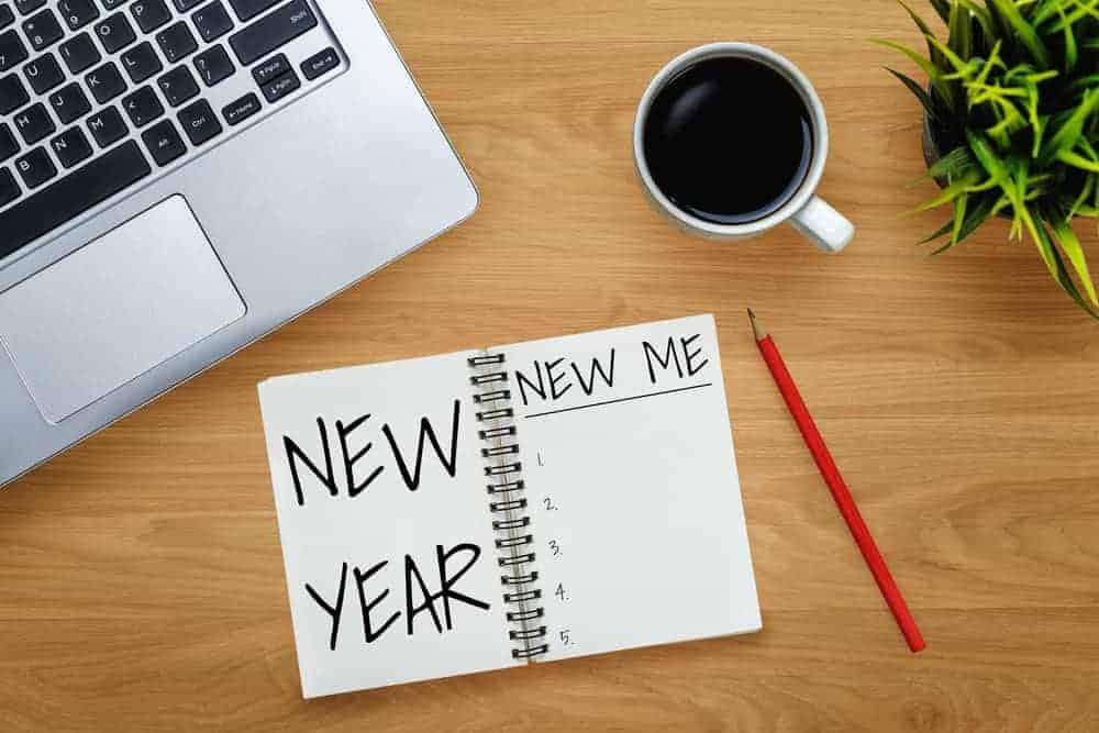 Gesunde Vorsätze 2021 Ziele Laptop Tasse Kaffee und Notizblock auf Schreibtisch