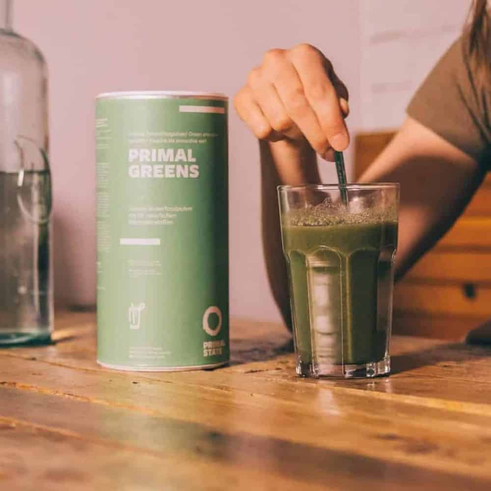 Junger Mann bereitet sich ein Glas Wasser mit Primal Greens Grünpulver zu